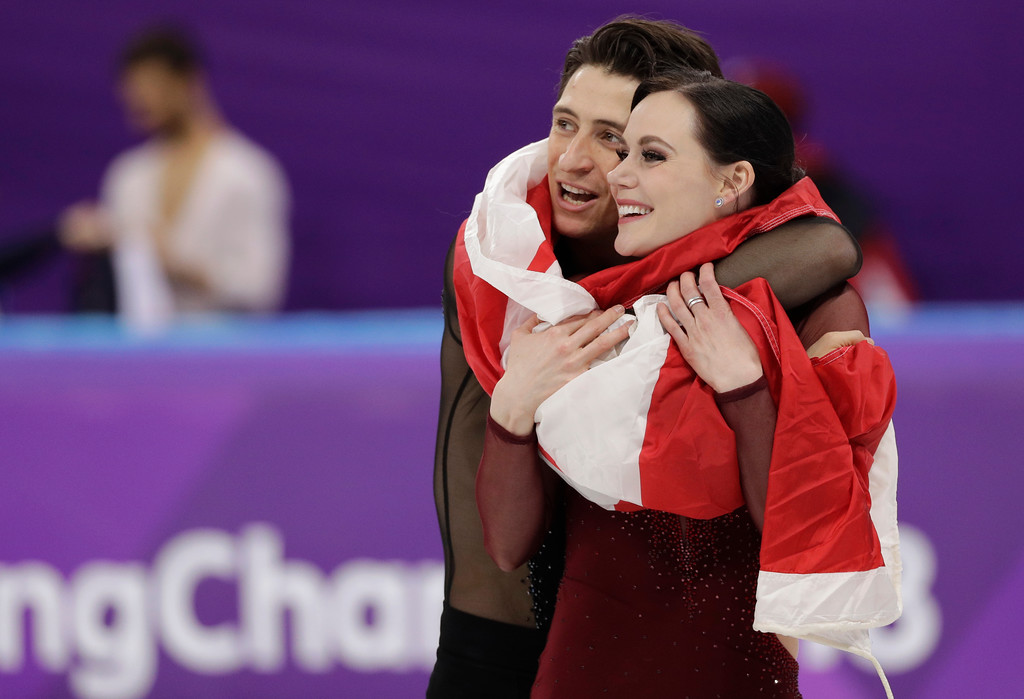 . Tessa Virtue and Scott Moir of Canada celebrate during the venue ceremony after winning the gold medal in the ice dance, free dance figure skating final in the Gangneung Ice Arena at the 2018 Winter Olympics in Gangneung, South Korea, Tuesday, Feb. 20, 2018. (AP Photo/David J. Phillip)