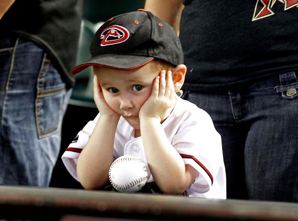 . A young Arizona Diamondbacks fan waits for the start of a MLB Opening Day National League baseball game between the Diamondbacks and the St. Louis Cardinals in Phoenix, Arizona April 1, 2013. REUTERS/Ralph D. Freso