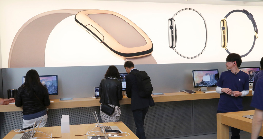 . Customers demonstrate Apple products in front of the advertisement wall of Apple Watch at an Apple Store in Tokyo as Apple Watch made its debut Friday, April 10, 2015. Customers were invited to try them on in stores and order them online. (AP Photo/Koji Sasahara)