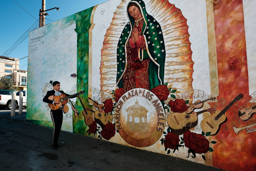 . A mariachi musician walks past a mural of the Virgin of Guadalupe as he arrives for the Santa Cecilia Festival in the Boyle Heights section of Los Angeles on Tuesday, Nov. 22, 2016. Musicians from around the country gathered for Mariachi Sol de Mexico to celebrate Santa Cecilia. The festival honors Santa Cecilia, the patron saint of musicians. (AP Photo/Richard Vogel)