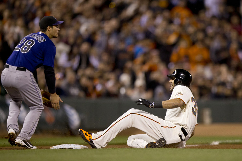 . Michael Morse #38 of the San Francisco Giants slides into third base for a triple in front of Nolan Arenado #28 of the Colorado Rockies during the fourth inning at AT&T Park on August 25, 2014 in San Francisco, California.  (Photo by Jason O. Watson/Getty Images)