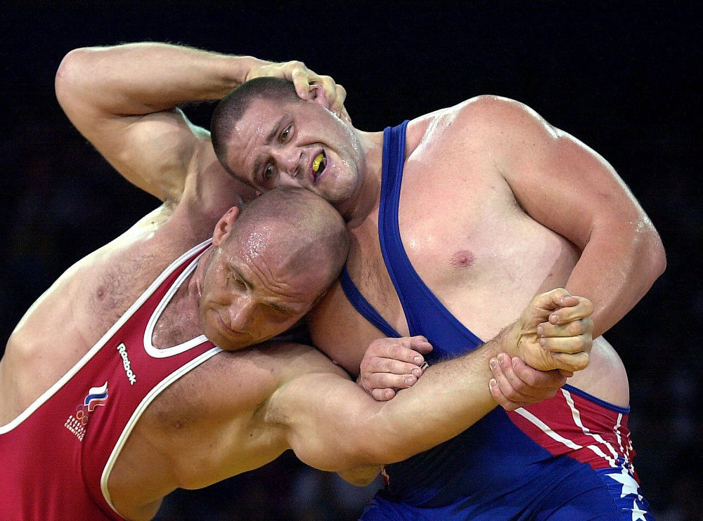 Description of . Kareline Alexandre of Russia (RED) attempts to power Rulon Gardner of the USA (BLUE) in the final of the men's 130kg Greco-Roman wrestling competition at the XXVII Olympic Summer Games 27 September 2000 in Sydney. American grizzly Gardner stopped giant Russian bear Karelin joining the ranks of Olympic immortals, shattering the defending champion's dreams of a fourth straight gold medal in a stunning upset. KIM JAE-HWAN/AFP/Getty Images