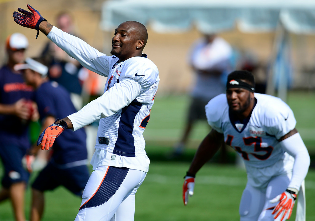 . Aqib Talib (21), left, can\'t help but do a little dancing as music plays over the loud speakers during warm-ups on Saturday. (Photo by Kathryn Scott Osler/The Denver Post)