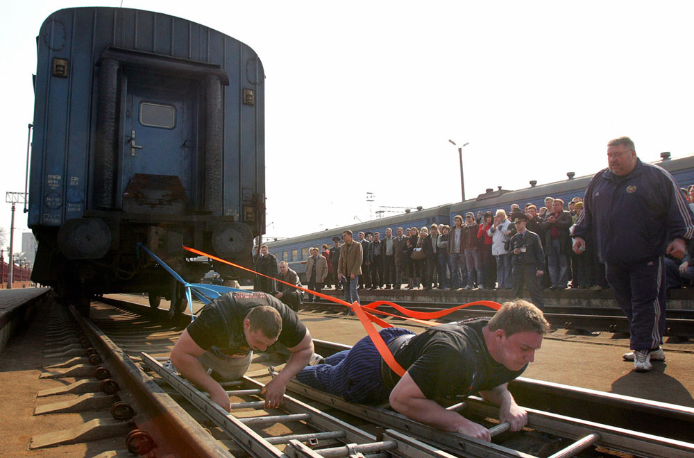 Description of . Minsk, BELARUS: Belarussian athletes Kirill Shimko (L) and Pavel Soroka pull five railway carriages, weighing altogether 250 tons, at Minsk central station, 30 March 2007. The pair moved the carriages over a 6,5 meter distance.  AFP PHOTO/ VIKTOR DRACHEV