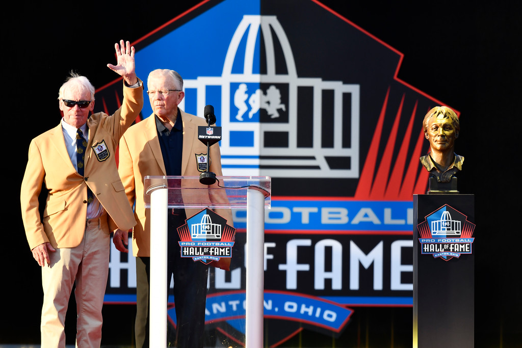 . Bobby Beathard, left, who was general manager for several NFL teams, waves while standing beside his presenter, Joe Gibbs, after his induction video was shown at the Pro Football Hall of Fame on Saturday, Aug. 4, 2018, in Canton, Ohio. (AP Photo/David Richard)