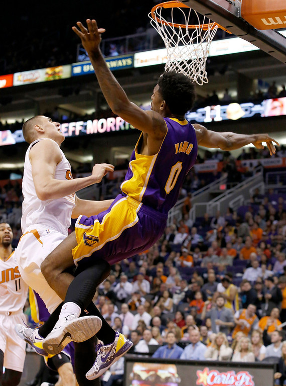 . Phoenix Suns\' Alex Len, left, of Ukraine, knocks Los Angeles Lakers\' Nick Young (0) to the ground for a flagrant foul as Young attempted a layup during the first half of an NBA basketball game Wednesday, Jan. 15, 2014, in Phoenix.  Both players were ejected from the game. (AP Photo/Ross D. Franklin)