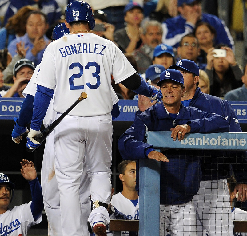 . Los Angeles Dodgers manager Don Mattingly high fives Carl Crawford and Adrian Gonzalez after Crwford scored on a sac fly ball by Gonxalez in the third inning of their baseball game against the San Diego Padres on Wednesday, April 17, 2013 in Los Angeles.   (Keith Birmingham/Pasadena Star-News)
