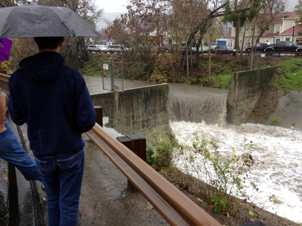 . Pedestrians watch the rushing water of a creek at Diablo Road and Front Street  through downtown Danville on Thursday.   (Jim Stevens/Bay Area News Group)