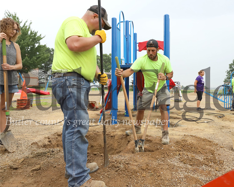 Dave Casile Snyder and Associates digs a post hole with volunteer Jason Zigler during Saturday's playground construction at Moraine Elementary. Seb Foltz/Butler Eagle 08/01/20