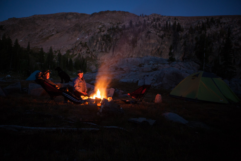 A camp cook and her son enjoy a quiet moment by the campfire during an archaeological project in the Tetons