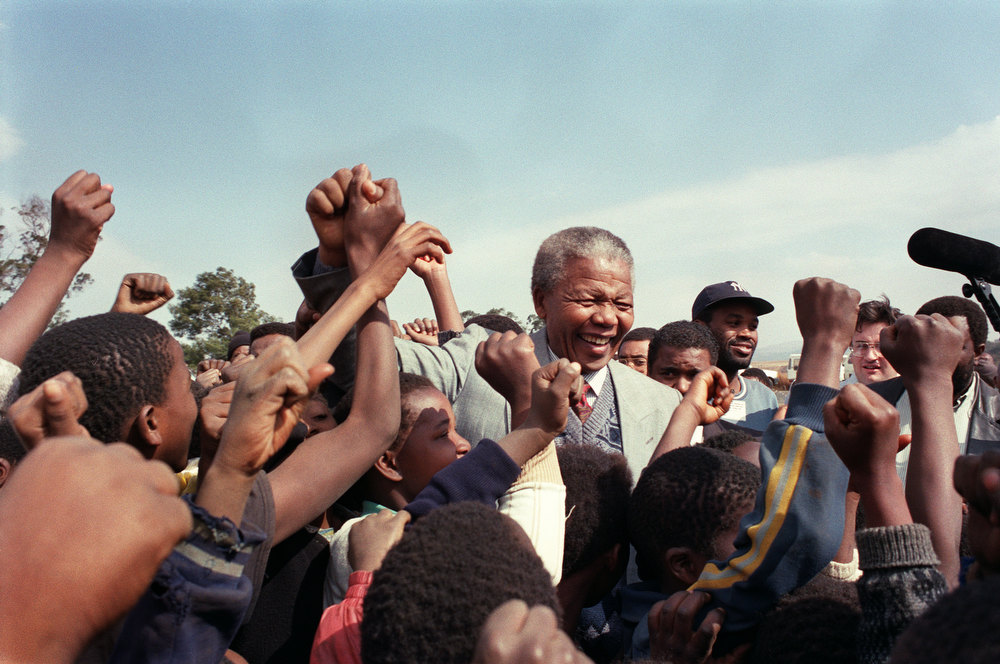 Description of . ANC president Nelson Mandela is surrounded by young supporters after addressing residents at Phola Park, a squatter settlement east of Johannesburg, 31 May 1992. In his speech, he attacked President Frederik W. de Klerk of being responsible for the violence that killed scores of people in black townships. (Photo credit should read WALTER DHLADHLA/AFP/Getty Images)