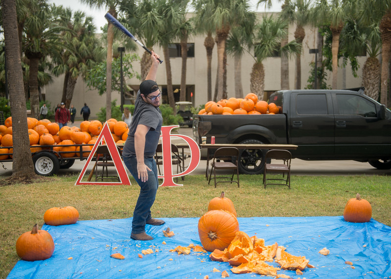 Student Kenneth Cantu uses a bat to smash a pumpkin during Omega Delta Phi's Pumpkin Smash event on the Center for Instruction Courtyard.