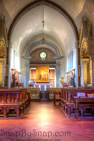 Fiesole, Italy – The Sanctuary – It is amazing what a little stained glass can do to the light in a room.  To my left is two small stained glass windows.  Inside the Gothic arch over the alter is bathed in natural light.  The two different light sources help to define the different spaces of this room.