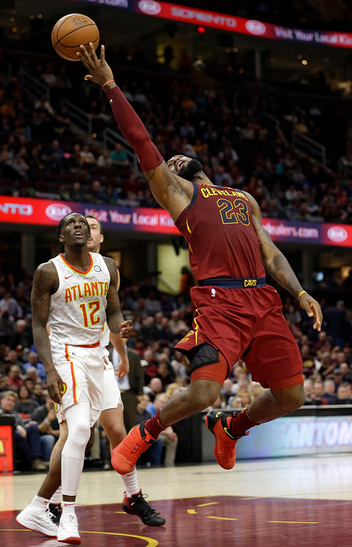 . Cleveland Cavaliers\' LeBron James, right, shoots over Atlanta Hawks\' Taurean Prince in the second half of an NBA basketball game, Tuesday, Dec. 12, 2017, in Cleveland. The Cavaliers won 123-114. (AP Photo/Tony Dejak)