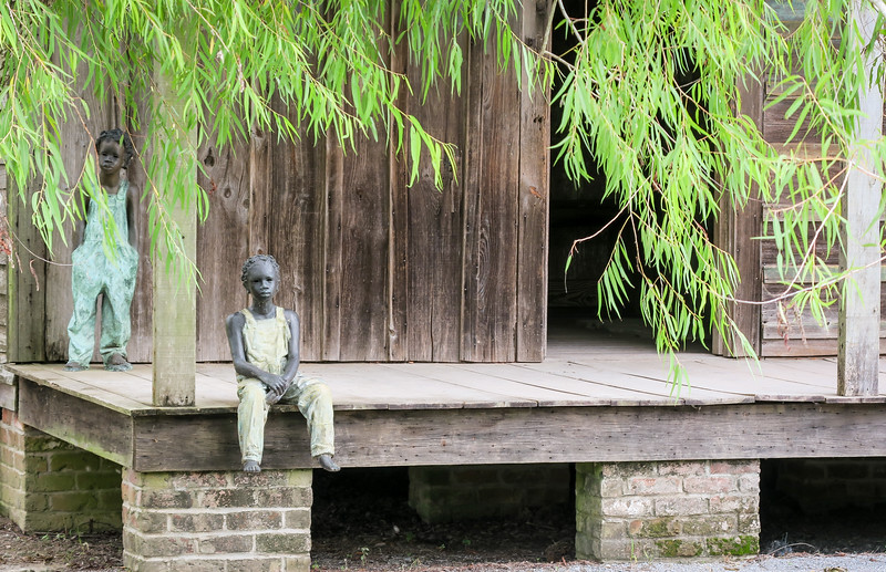 a wooden deck with two statues of small children