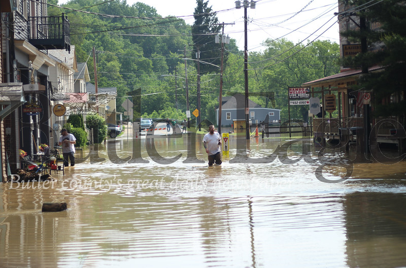 Wunderbar co-owner Seth Murphy, left, and Center of Harmony owner Josh Meeder, right, wade through floodwaters on Mercer Street in Harmony. Murphy said this is the worst flooding he's seen.