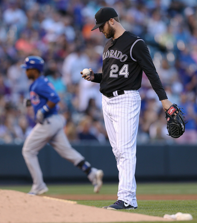 . Colorado Rockies starting pitcher Jordan Lyles front, looks over new ball as Chicago Cubs\' Arismendy Alcantara, back, circles the bases after hitting a two-run home run in the fourth inning of a baseball game in Denver on Wednesday, Aug. 6, 2014. (AP Photo/David Zalubowski)