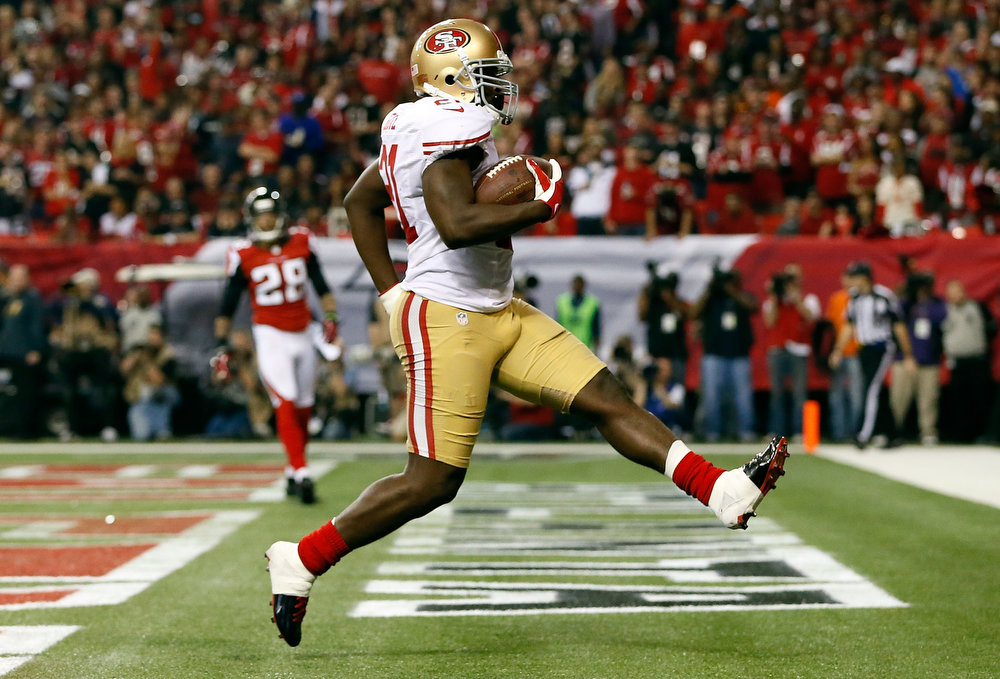 Description of . Frank Gore #21 of the San Francisco 49ers scores a 5-yard rushing touchdown in the third quarter against the Atlanta Falcons in the NFC Championship game at the Georgia Dome on January 20, 2013 in Atlanta, Georgia.  (Photo by Kevin C. Cox/Getty Images)