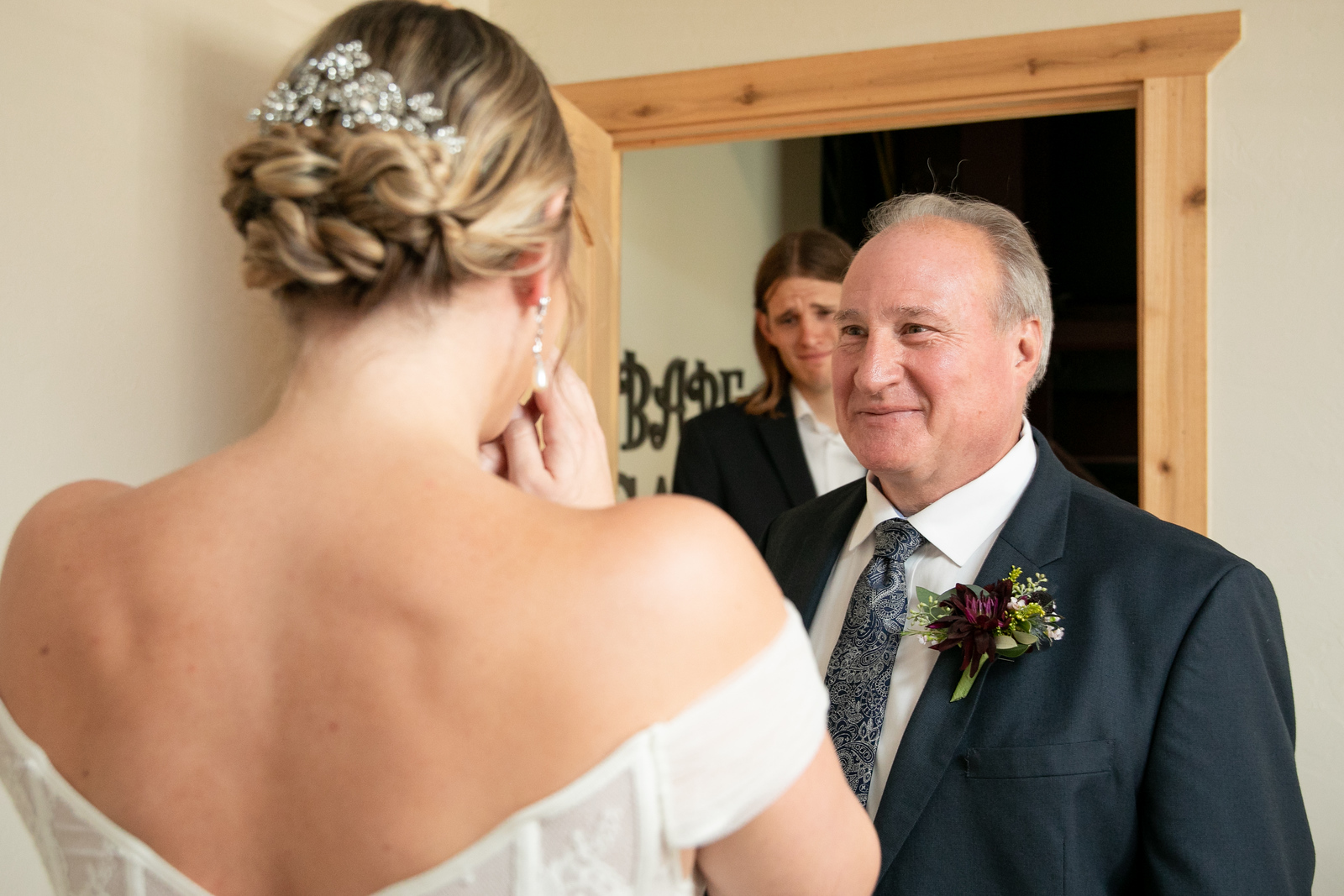 father smiling as he sees his daughter in her wedding dress for the first time