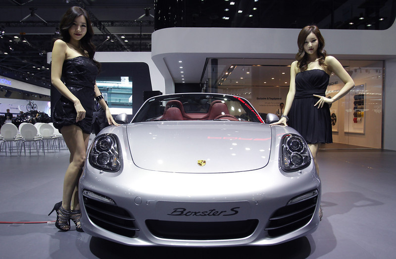 . Models pose next to a Porsche Boxster S at the Seoul Motor Show 2013 on March 28, 2013 in Goyang, South Korea. The Seoul Motor Show 2013 will be held in March 29-April 7, featuring state-of-the-art technologies and concept cars from global automakers. The show is its ninth since the first one was held in 1995. About 384 companies from 14 countries, including auto parts manufacturers and tire makers, will set up booths to showcase trends in their respective industries, and to promote their latest products during the show.  (Photo by Chung Sung-Jun/Getty Images)