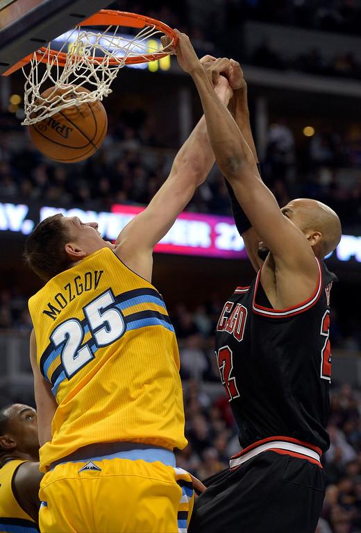 . Chicago Bulls power forward Taj Gibson (22) shams one through over Denver Nuggets center Timofey Mozgov (25) during the third quarter November 21, 2013 at Pepsi Center. (Photo by John Leyba/The Denver Post)