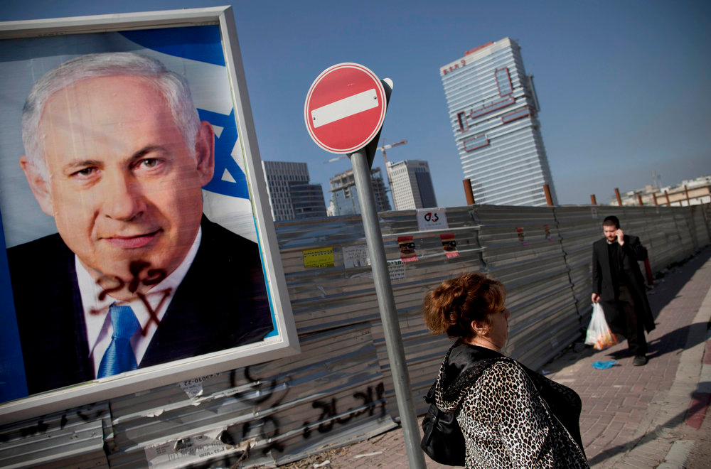 . Israelis walk past an election campaign billboard of Israeli Prime Minister and Likud Party leader Benjamin Netanyahu, in Givataim, Israel, Sunday, Jan. 20, 2013. General elections in Israel are scheduled for Jan. 22, 2013. (AP Photo/Oded Balilty)