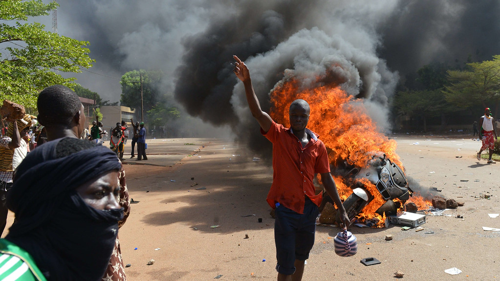 . Protesters stand outside the parliament in Ouagadougou on October 30, 2014 as cars and documents burn outside. ISSOUF SANOGO/AFP/Getty Images