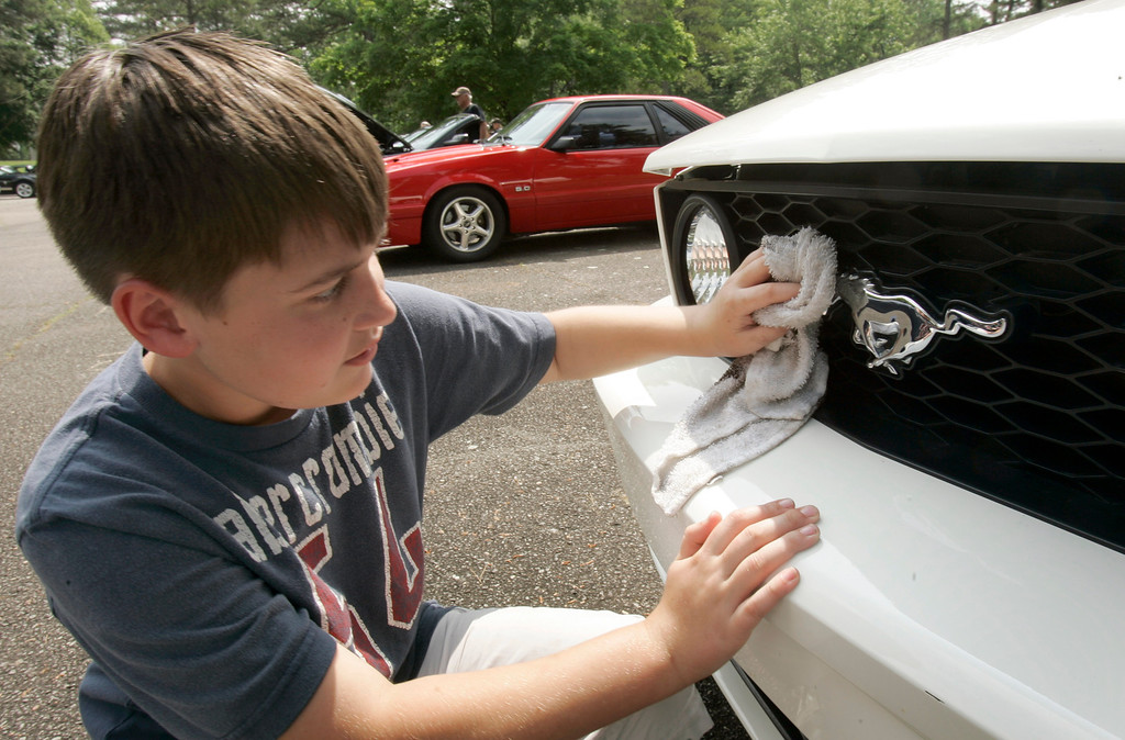 ". Aaron Heath, 11, polishes the galloping horse emblem on his father Ford Mustang during the ""Mustangs on the Mountain\"" gathering at the Museum of Automobiles on Petit Jean Mountain near Morrilton, Ark., Sunday, May 25, 2008. About 70 owners and drivers of the cars attend the event annually. (AP Photo/Danny Johnston)"