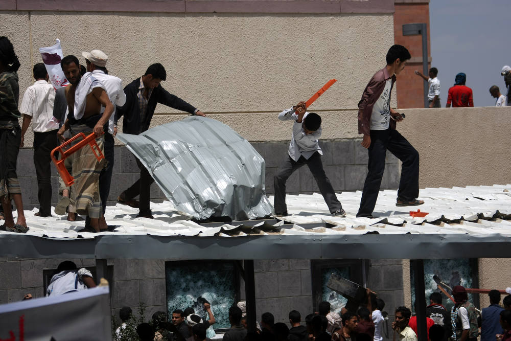 Description of . Yemeni protesters try to break through the US embassy in Sanaa during a protest over a film mocking Islam on September 13, 2012. Yemeni forces managed to drive out angry protesters who stormed the embassy in the Yemeni capital with police  firing warning shots to disperse thousands of people as they approached the main gate of the mission.   AFP PHOTO/MOHAMMED  HUWAIS/AFP/Getty Images