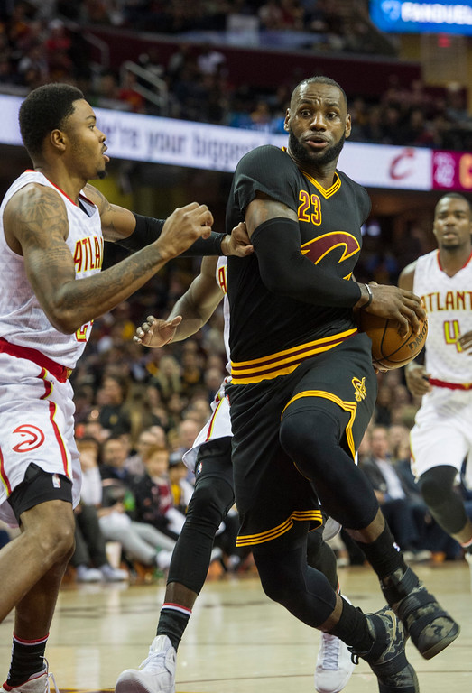. Cleveland Cavaliers\' LeBron James (23) drives to the basket as Atlanta Hawks\' Kent Bazemore (24) defends during the second half of an NBA basketball game in Cleveland, Tuesday, Nov. 8, 2016. The Hawks won 110-106. (AP Photo/Phil Long)