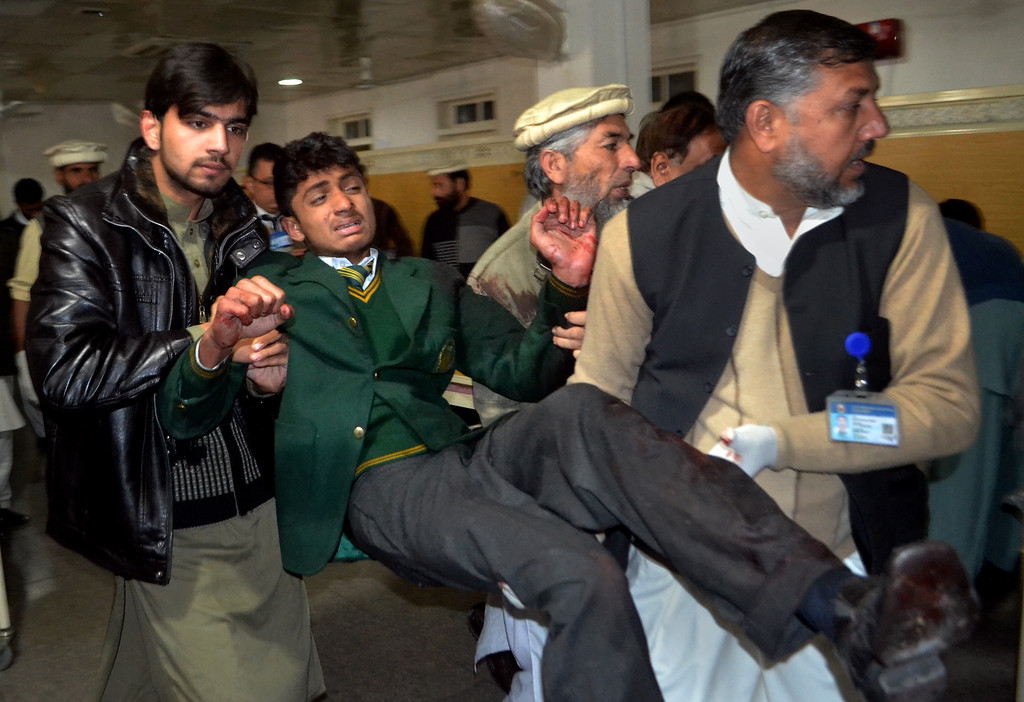 . Pakistani volunteers carry a student injured in the shootout at a school under attack by Taliban gunmen, at a local hospital in Peshawar, Pakistan,Tuesday, Dec. 16, 2014. Taliban gunmen stormed a military school in the northwestern Pakistani city, killing and wounding dozens, officials said, in the latest militant violence to hit the already troubled region. (AP Photo/Mohammad Sajjad)