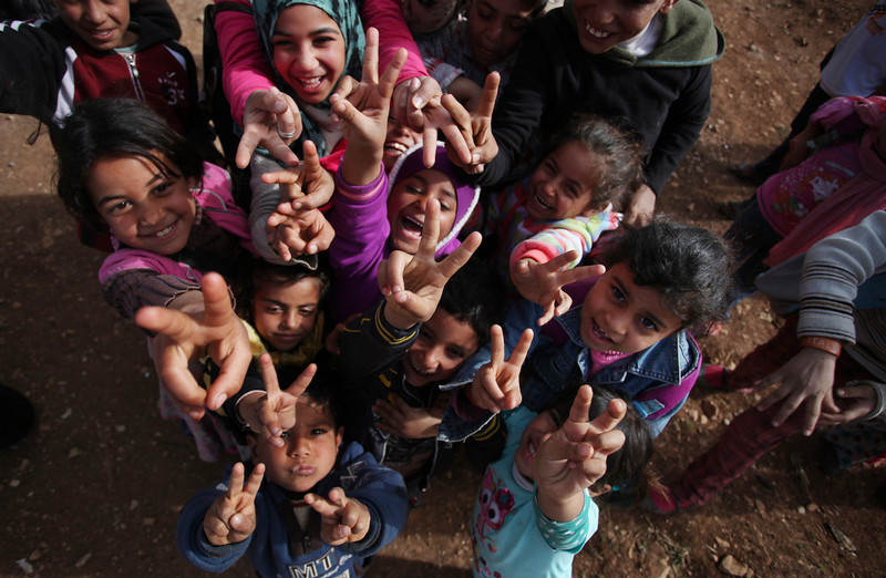 . Syrian refugees pose for a photo as flashing v-signs at an unofficial refugee camp on the outskirts of Amman, Jordan, Wednesday, Jan. 22, 2014. Peace talks intended to carve a path out of Syria\'s civil war got off to a rocky start Wednesday as a bitter clash over President Bashar Assad\'s future threatened to collapse the negotiations even before they really begin. Later this week in Geneva, Syria\'s warring sides will sit down for their first face-to-face meeting since the conflict erupted. (AP Photo/Mohammad Hannon)