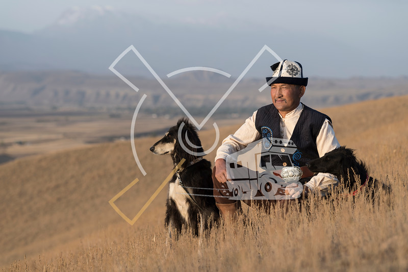 Kyrgyz man posing with his hunting dogs outdoors in Kyrgyzstan.