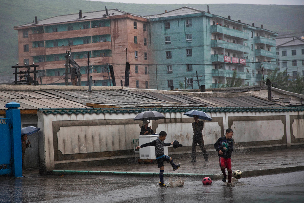 """. In this June 16, 2014 photo, boys play soccer in the town of Hyesan in North Korea\'s Ryanggang province. The Associated Press was granted permission to embark on a weeklong road trip across North Korea to the countryís spiritual summit Mount Paektu. The trip was on North Korea\'s terms. An AP reporter and photographer couldn\'t interview ordinary people or wander off course, and government \""""minders\"""" accompanied them the entire way. (AP Photo/David Guttenfelder)"""