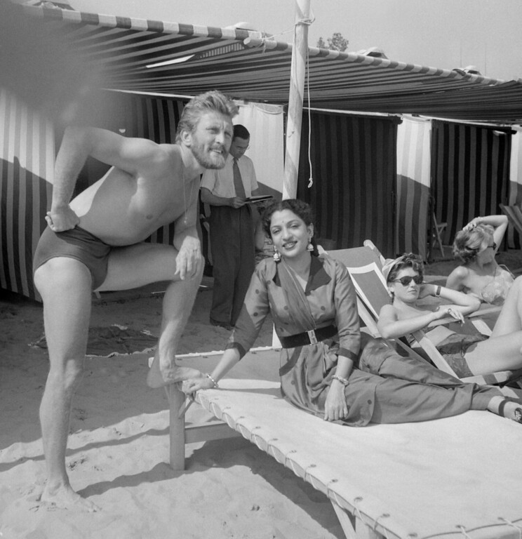 . VENICE, ITALY:  Film actor Kirk Douglas and the Indian actress Mehtab rest at the Lido beach, 01 September 1953, during the Venice Film Festival. Douglas born in Amsterdam, Netherlands, made his Broadway debut in 1941, served in the US Navy and embarked on a screen career in 1946. His films include Champion (1949), The bad and the Beautiful (1952), Lust for Life (1956)j, and Spartacus (1960). From the 1970s Douglas also worked as director. AFP/AFP/Getty Images