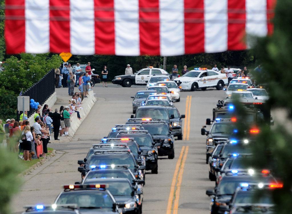 . A procession of police cars enter Acacia Park Cemetery.  (Pioneer Press: Jean Pieri)