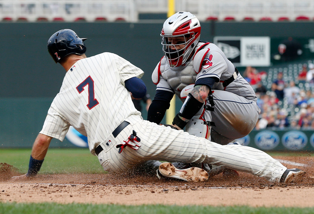 . Minnesota Twins\' Joe Mauer, left, is tagged out at the plate by Cleveland Indians catcher Roberto Perez for a double play hit into by Eddie Rosario during the third inning of the second game of a baseball doubleheader Thursday, Aug. 17, 2017, in Minneapolis. (AP Photo/Jim Mone)