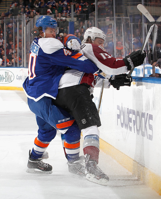 . UNIONDALE, NY - FEBRUARY 08:  Michael Grabner #40 of the New York Islanders dodges the puck near his head as he checks P.A. Parenteau #15 of the Colorado Avalanche during the first period of an NHL hockey game at Nassau Veterans Memorial Coliseum on February 8, 2014 in Uniondale, New York.  (Photo by Paul Bereswill/Getty Images)