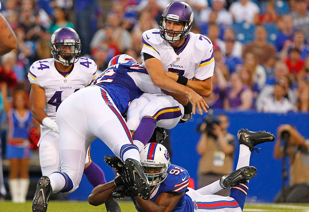 . Minnesota Vikings\' Christian Ponder (7) is hit by Buffalo Bills\' Alex Carrington (92) and Manny Lawson (91) while throwing the ball during the first half of an NFL preseason football game Friday, Aug. 16, 2013, in Orchard Park, N.Y.  (AP Photo/Bill Wippert)