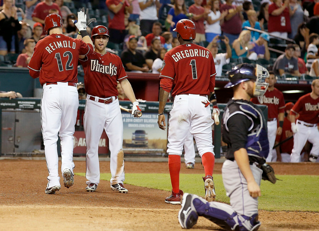 . Arizona Diamondbacks\' Nolan Reimold (12) celebrates his two-run home run with teammates Didi Gregorius (1) and Ender Inciarte, as Colorado Rockies\' Jackson Williams, right, kneels next to home plate during the seventh inning of a baseball game Sunday, Aug. 31, 2014, in Phoenix. (AP Photo/Ross D. Franklin)