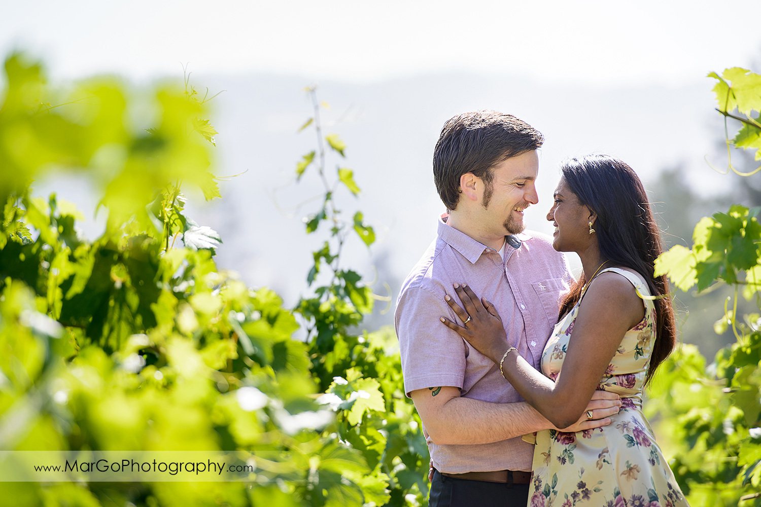 man in pink shirt and Indian woman in flower dress looking at each other in the vineyard during engagement session at Castello di Amorosa in Calistoga