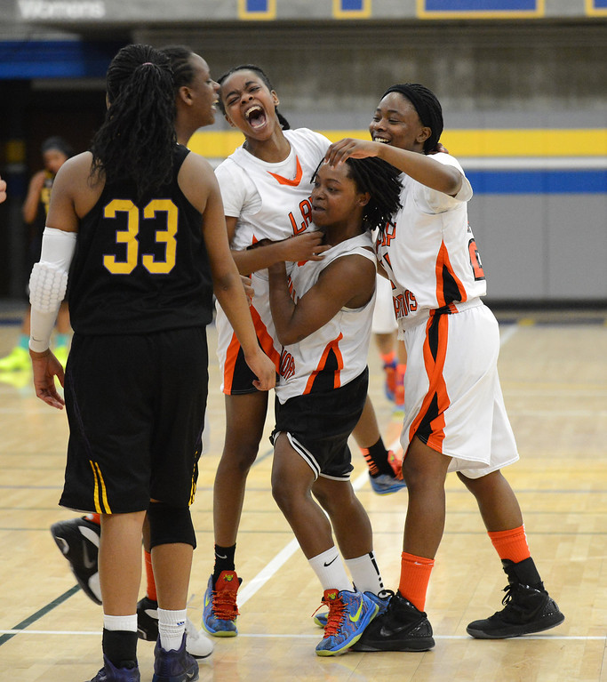. McClymonds High\'s Gabby Gaines (1), center, celebrates with teammates following their victory over Oakland Tech High in their Oakland Section high school girls basketball championship game played at Merritt College in Oakland, Calif. on Thursday, Feb. 28, 2013. (Dan Honda/Staff)