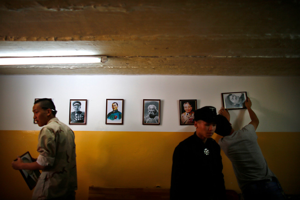 . Members of the Mongolian neo-Nazi group Tsagaan Khass hang up portraits of Mongolian heroes at the group\'s headquarters in Ulan Bator June 24, 2013. The group has rebranded itself as an environmentalist organisation fighting pollution by foreign-owned mines, seeking legitimacy as it sends Swastika-wearing members to check mining permits. Over the past years, ultra-nationalist groups have expanded in the country and among those garnering attention is Tsagaan Khass, which has recently shifted its focus from activities such as attacks on women it accuses of consorting with foreign men to environmental issues, with the stated goal of protecting Mongolia from foreign mining interests. This ultra-nationalist group was founded in the 1990s and currently has 100-plus members. Picture taken June 24, 2013. REUTERS/Carlos Barria