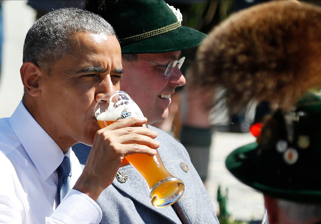. U.S. President Barack Obama drinks a beer as he sits between men dressed in traditional Bavarian clothes during a visit to the village of Kruen, southern Germany, Sunday, June 7, 2015 prior to the G-7 summit in Schloss Elmau hotel near Garmisch-Partenkirchen where the summit will start later the day. (AP Photo/Markus Schreiber)
