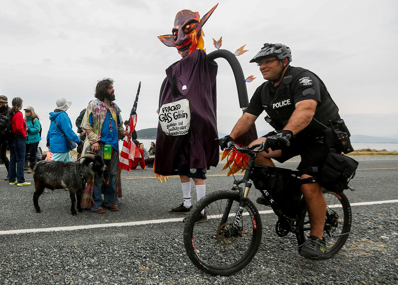 Man and goat chat with Fracked Gas Goblin as a police officer passes at the demonstration outside the Anacortes oil refinery during the Break-Free Pacific Northwest protest on May 14, 2016.