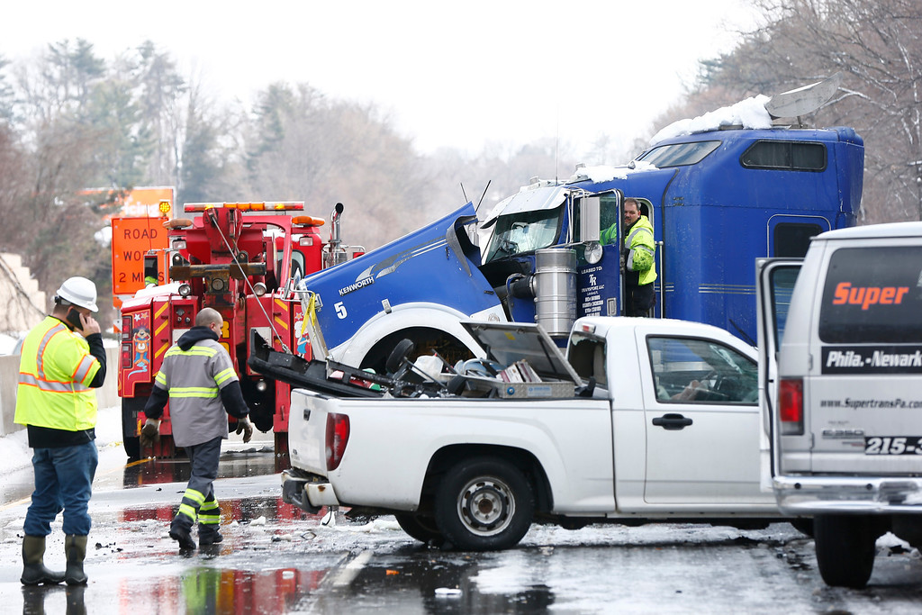 . Workers remove vehicles piled up in an accident, Friday, Feb. 14, 2014, in Bensalem, Pa. Traffic accidents involving multiple tractor trailers and dozens of cars have completely blocked one side of the Pennsylvania Turnpike outside Philadelphia and caused some injuries. (AP Photo/Matt Rourke)