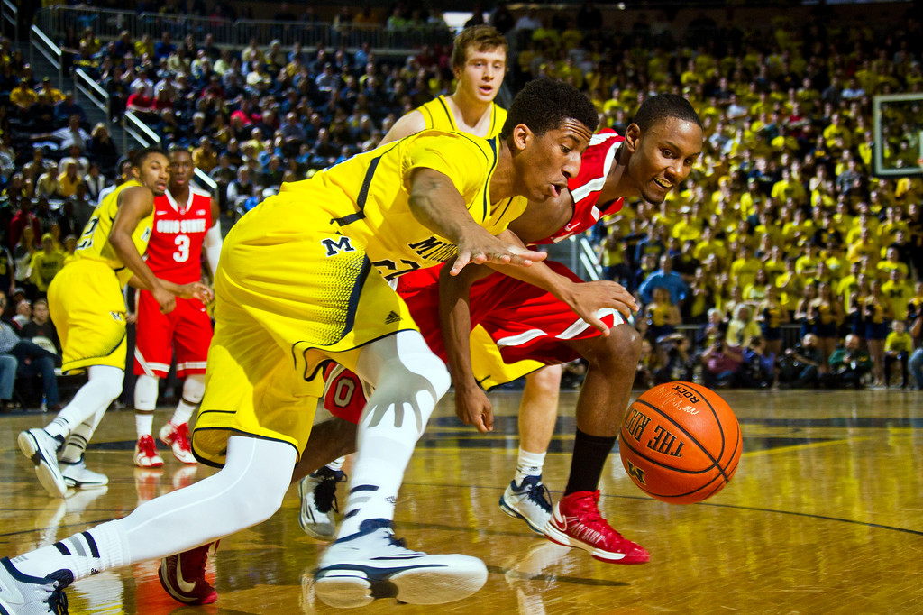 . Michigan guard guard Aubrey Dawkins, front, scrambles for the ball with Ohio State forward Sam Thompson, right, in the first half of an NCAA college basketball game at Crisler Center in Ann Arbor, Mich., Sunday, Feb. 22, 2015. (AP Photo/Tony Ding)
