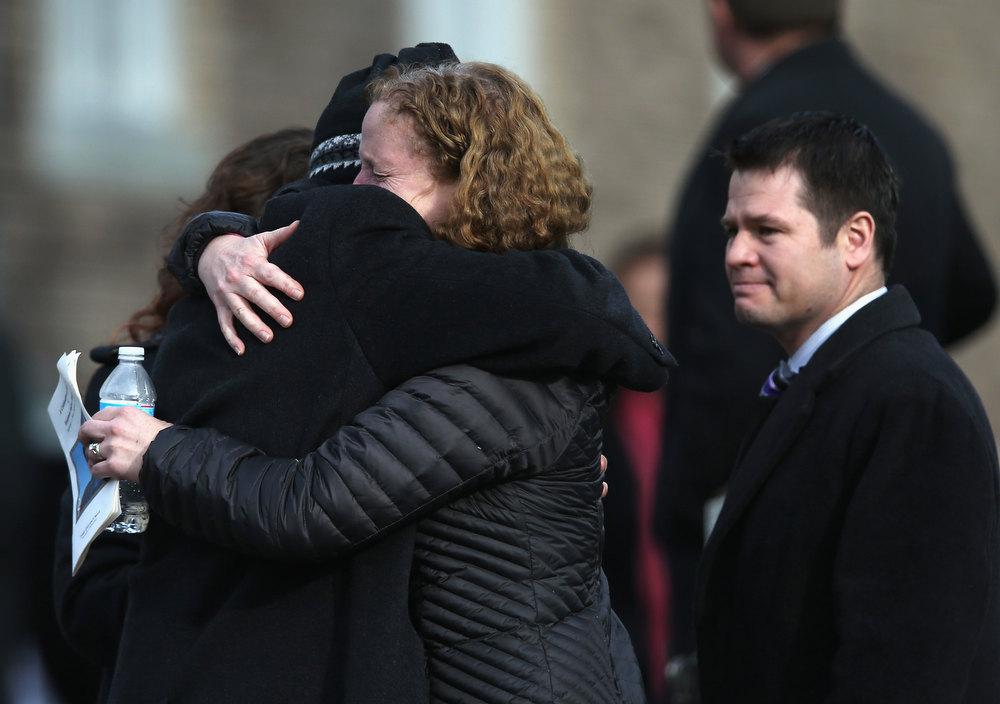 . Mourners embrace following a funeral for Benjamin Wheeler, 6, at the Trinity Episcopal Church on December 20, 2012 in Newtown, Connecticut. Benjamin, a member of Tiger Scout Den 6, was killed when 20 children and six adults were massacred at Sandy Hook Elementary School last Friday. Six services were held for students and teachers in the Newtown area Thursday.  (Photo by John Moore/Getty Images)