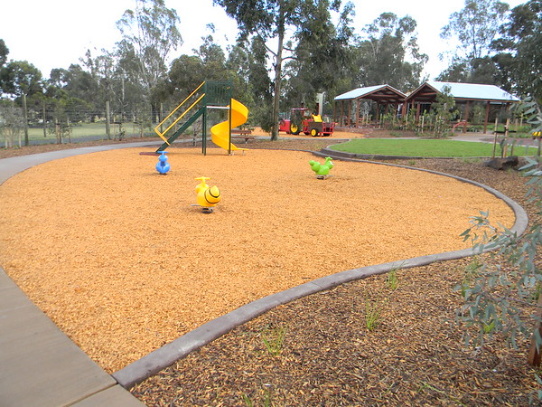 blue, yellow and green spring rockers in mulch softfall and green and yellow spiral slide with shade structures and tractor