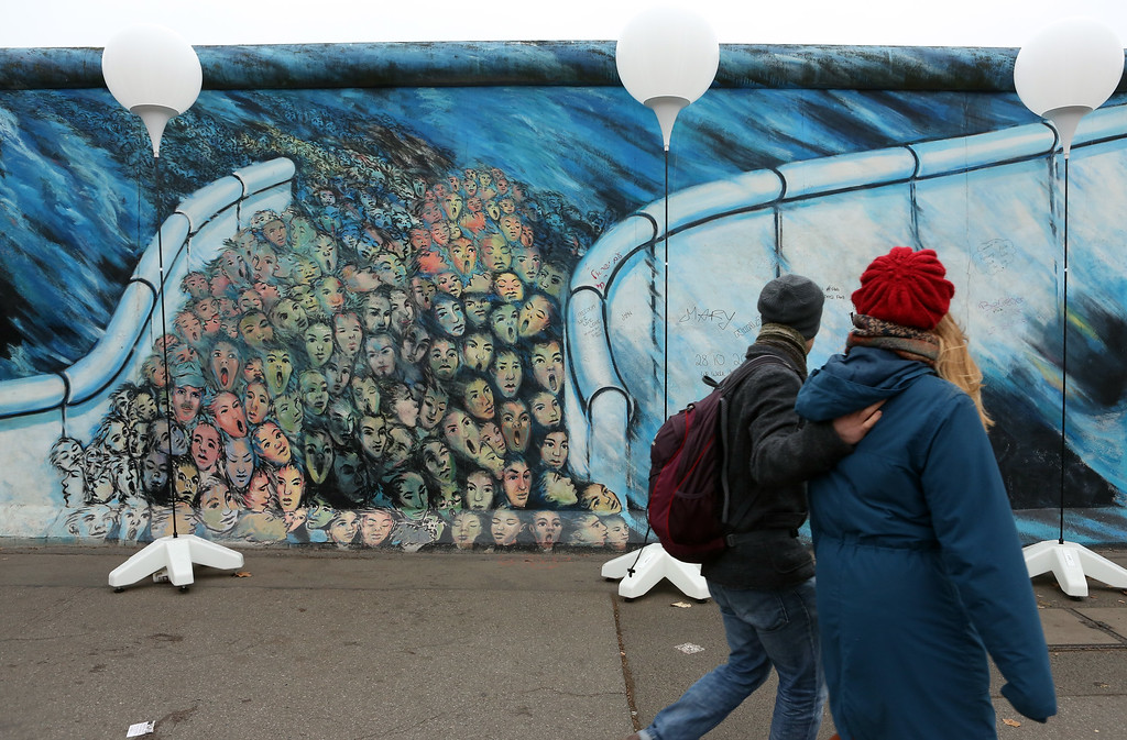 . BERLIN, GERMANY - NOVEMBER 09:  Visitors walk by East Side Gallery, a section of the former Berlin Wall, during celebrations for the 25th anniversary of the fall of the Wall on November 9, 2014 in Berlin, Germany. The city of Berlin is commemorating the 25th anniversary of the fall of the Berlin Wall from November 7-9 with an installation of 6,800 lamps coupled with illuminated balloons along a 15km route where the Wall once ran and divided the city into capitalist West and communist East. The fall of the Wall on November 9, 1989, was among the most powerful symbols of the revolutions that swept through the communist countries of Eastern Europe and heralded the end of the Cold War. Built by the communist authorities of East Germany in 1961, the Wall prevented East Germans from fleeing west and was equipped with guard towers and deadly traps.  (Photo by Adam Berry/Getty Images)